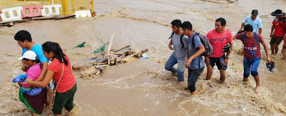 """This handout photo released by Peru's Andina news agency shows local residents in a poor neighbourhood on the outskirts of Lima wading along a flooded avenue on March 16, 2017, after unusually heavy rainfall caused flash floods in the arid coastal region and the foothills of the Andes. / AFP PHOTO / ANDINA / HO / XGTY   /  RESTRICTED TO EDITORIAL USE-MANDATORY CREDIT """"HANDOUT/AFP PHOTO/ANDINA NEWS AGENCY/JUAN CARLOS GUZMAN"""" NO MARKETING NO ADVERTISING CAMPAIGNS-DISTRIBUTED AS A SERVICE TO CLIENTS-GETTY OUT"""